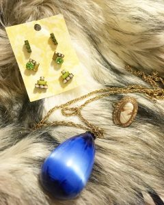Picture of blue necklace, three sets of green earrings, and a vintage ring against a fur background