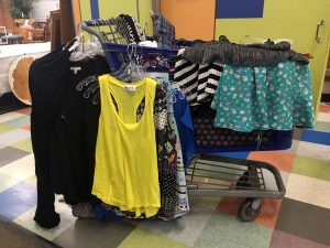 A Goodwill cart filled with clothing items with shirts and skirts hanging on the side