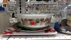 A vintage, white bowl with a brown mushroom design sitting on top of a few plates on a Goodwill shelf