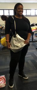 A woman in black pants and black shirt with a large silver purse