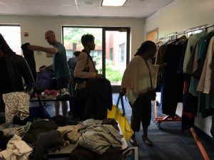 A picture of the DCGF Swap attendees looking through the items that are being swapped. Most of the items are clothing and are placed on tables.