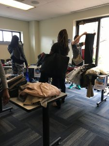 A picture of the DCGF Swap attendees looking through the items that are being swapped. Most of the items are clothing and are placed on tables and on racks