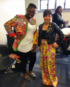 A picture of two women: the DCGF in a floral long skirt and leather jacket and another woman in a brightly patterned jacket, black pants, white shirt, and black glasses