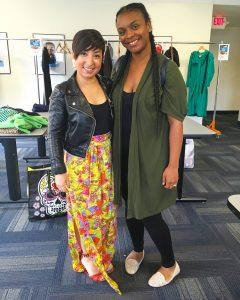A picture of two women: the DCGF in a floral long skirt and leather jacket and a second woman in a long dark green jacket, black pants, and black shirt
