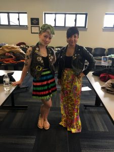 A picture of two women: the DCGF in a floral long skirt and leather jacket and a second woman in a black, green, orange, red, green, and blue striped skirt, and sleeveless jacket with patches, a black shirt, and multiple tattoos