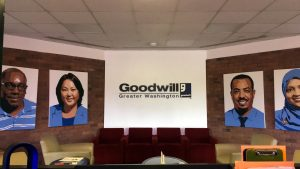 A picture of the front desk of the Goodwill of Greater Washington Headquarters. On the back wall there is a Goodwill of Greater Washington logo and for painted pictures of people who have been served by Goodwill of Greater Washington