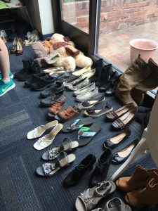 A picture with dozens of pairs of different kinds of shoes in front of a window