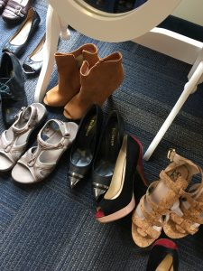A picture of multiple pairs of shoes: a tan pair of short heel boots, silver sandals, black heels, and tan sandal heels