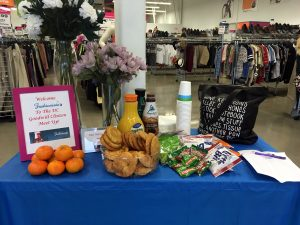 A table with a blue cloth on it at the front of the Clinton Goodwill retail store in front of a cash register with snacks like cookies, oranges, muffins, and orange juice with a sign welcoming the attendees of the MeetUp