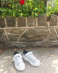 A picture of a pair of grey, platform, sneakers outside in front of a stone wall and flower bushes