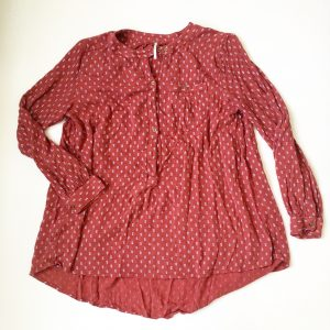 A picture of a Free People pumpkin colored blouse with gold buttons and small, white, geometric, stitch designs