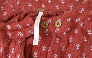 A picture of a Free People pumpkin colored blouse with gold buttons and small, white, geometric, stitch designs (A closeup of the tags which tell the blouse is extra small)