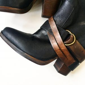 A picture of a pair of Steve Madden high boots with brown leather straps and buckles (a close up of the straps and buckles