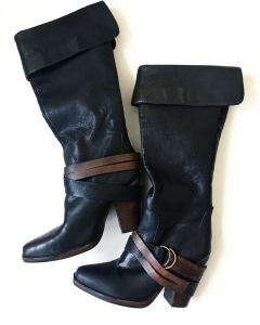 A picture of a pair of Steve Madden high boots with brown leather straps and buckles