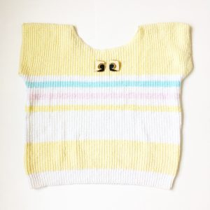 A picture of a sleeveless striped sweater that is a pale yellow, blue, pink, and white. On top of the sweater is a pair of artsy, stud, black and cream earrings with gold outlining