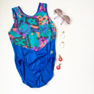 A picture of a woman's one piece bathing suit: the bottom half is blue and the top half is a combination of tropical colors in geometric shapes and palm trees. Also pictured is a pair of purple rimmed sunglasses, white circle dangle earrings, and pink circle dangle earrings