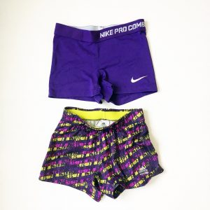 A picture of two pairs of woman's workout shorts: the pair on top are Nike ProCombat and are solid purple. the bottom are Adidas dark and light purple with a bright yellow color