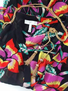 A picture of a sleeveless, black, button up, blouse with a floral patterm with a gold tassel necklace with glass beads on top of it