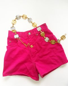 A picture of hot pink shorts with a gold and silver belt