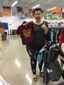 Picture of a woman at the Clinton Goodwill retail location with a cart full of items holding up a child's Ben's Chili Bowl shirt