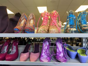 A picture of different kinds of colorful shoes at the Waldorf Goodwill of Greater Washington retail location. These include pink heels, two pairs of boots, one with pink laces and the other with blue, multicolored heels, and purple heels