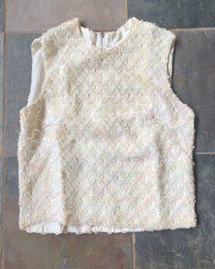 A cream colored sequin sleeveless shirt