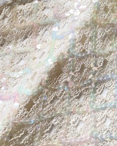 A close up of the sequins on the cream sleeveless shirt