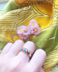 A picture of a hand wearing a multicolored gold ring, a pair of flower clip on earrings, and yellow patterned napkins