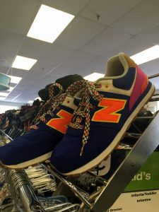 A picture of New Balance shoes, the primary color is dark blue, the N logo is a bright orange, and the heel is purple