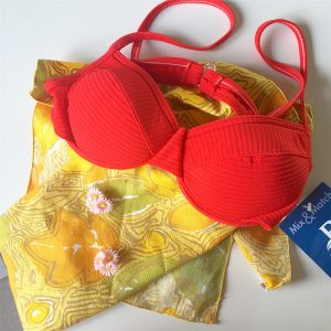 A picture of a woman's red bathing suit top laying on a yellow floral patterned napkins
