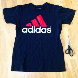 A picture of an Adidas t-shirt, it is blue with a pink three strip logo with the word adidas under the logo. There is also a pair of scissors sitting next to the shirt