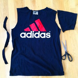 A picture of an Adidas t-shirt, it is blue with a pink three strip logo with the word adidas under the logo. There is also a pair of scissors sitting next to the shirt. The sleeves of the shirt have been cut off
