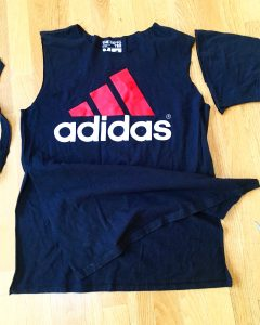 A picture of an Adidas t-shirt, it is blue with a pink three strip logo with the word adidas under the logo. There is also a pair of scissors sitting next to the shirt. The sleeves of the shirt have been cut off and the front has now been cut on both sides to create a flap in front