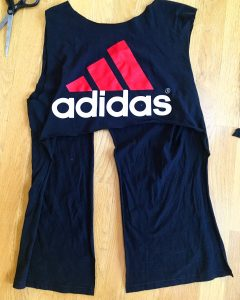 A picture of an Adidas t-shirt, it is blue with a pink three strip logo with the word adidas under the logo. There is also a pair of scissors sitting next to the shirt. The sleeves of the shirt have been cut off and the front has now been cut on both sides. The flap has now been cut and a segment has been cut out of the back to create two strips still attached to the shirt