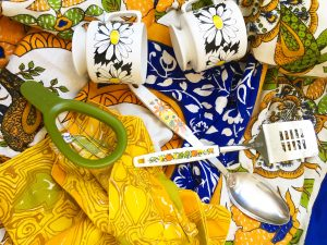 Two white coffee mugs with flowers printed on them, a green avocado cuber, a spatula and serving spoon with white handles that have floral patterns on them on top of an ornate blue table cloth and yellow patterned napkins