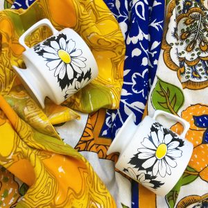 Two white coffee mugs with flowers printed on them on top of an ornate blue table cloth and yellow patterned napkins