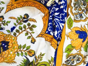 A table cloth with an ornate blue, white, and gold pattern with a print of a plant on it