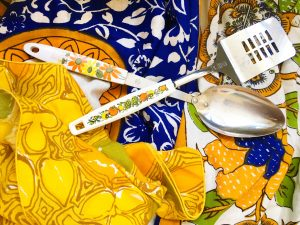 A spatula and serving spoon with white handles that have floral patterns on them on top of an ornate blue table cloth and yellow patterned napkins
