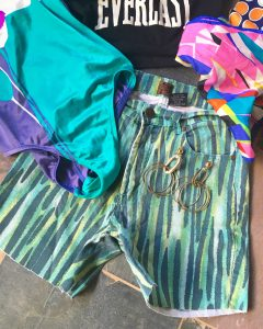 A picture of blue and green striped patterned high waisted short that have been converted from pants surrounded by a black, Everlast crop top shirt, pink patterned scarf, a retro one piece bathing suite, and gold earrings