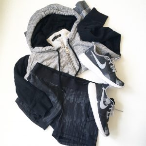 A picture of three items: a size medium, comfy, soft gray and black, paneled hoodie by Rag and Boone, stretchy, elastic, black Lululemon fitness mini running shorts in a size 8, and a pair of Nike, grey, black, and white monochromatic running shoes