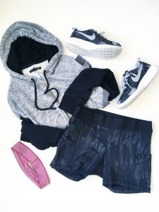 A picture of four items: a size medium, comfy, soft gray and black, paneled hoodie by Rag and Boone, stretchy, elastic, black Lululemon fitness mini running shorts in a size 8, a pair of Nike, grey, black, and white monochromatic running shoes, and a pink headband