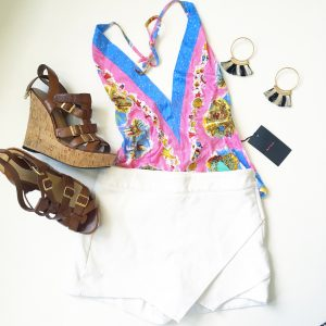 A picture of a pink holter top with beach prints on it; leather strap, cork wedge sandals, a white skort, and a pair of hoop earrings that have black and white tassels on them