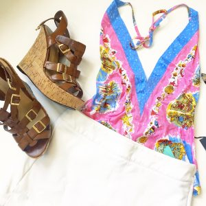 A picture of a pink holter top with beach prints on it; leather strap, cork wedge sandals, a white skort