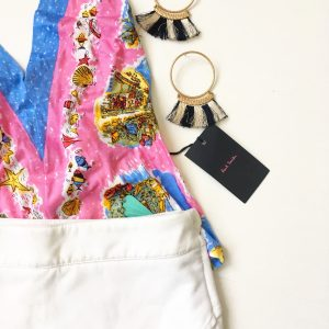 A picture of a pink holter top with beach prints on it; a white skort, and a pair of hoop earrings that have black and white tassels on them