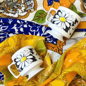 A picture of two white mugs with flowers on them. They are laying on top of a colorful table cloth
