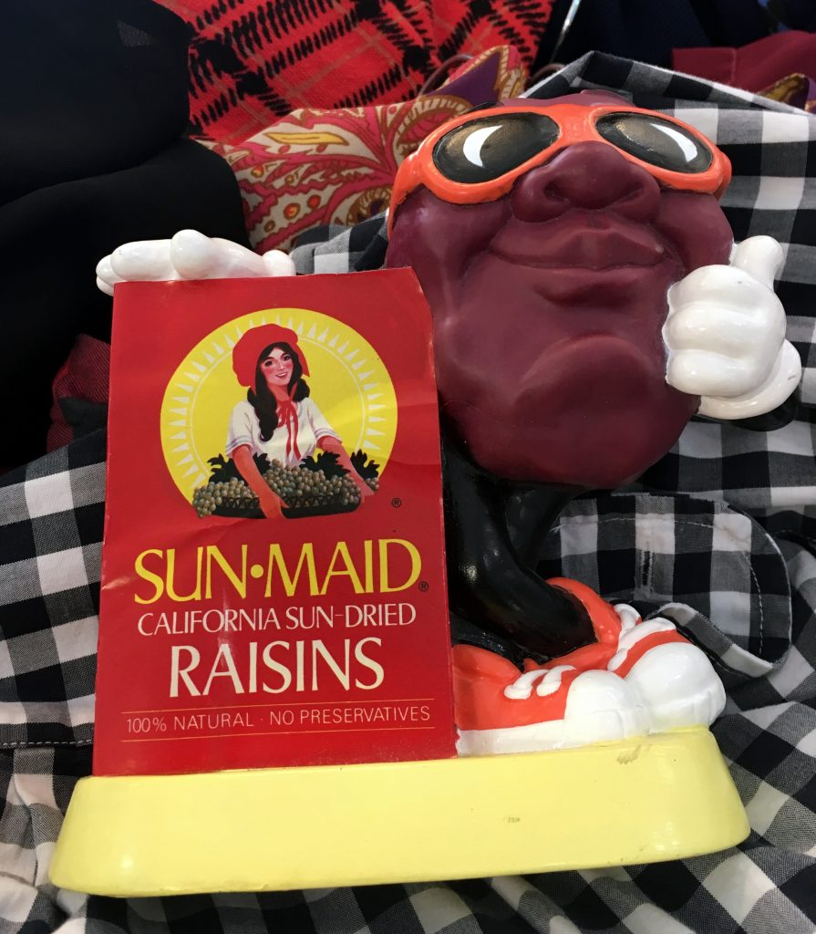A picture of a 1980's Sun Maid raisin bank with a raisin character in sunglasses on it