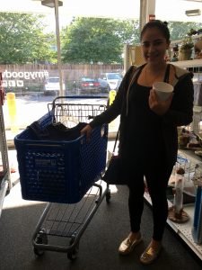 A picture of a woman in black shopping next to a blue Goodwill of Greater Washington shopping cart. She is holding a white mug