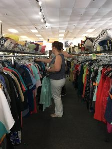 A woman in white pants and a sleeveless shirt shopping the racks at the Alexandria Goodwill of Greater Washington retail store