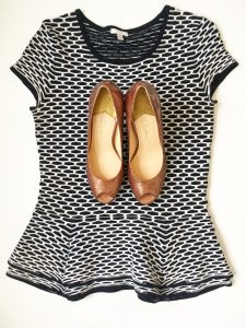 A picture of a top that is a stretchy, black and white, short sleeved, peplum blouse by Intermix in a size medium. On top of the shirt is a pair of reddish, warm gold, metallic, short, open-toed, modern, Cole Haan heels in a size 7