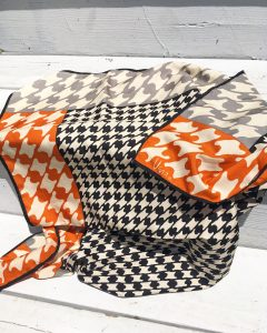 A vintage silk scarf with a black, white, and orange houndstooth patter on it laying on a set of white stairs